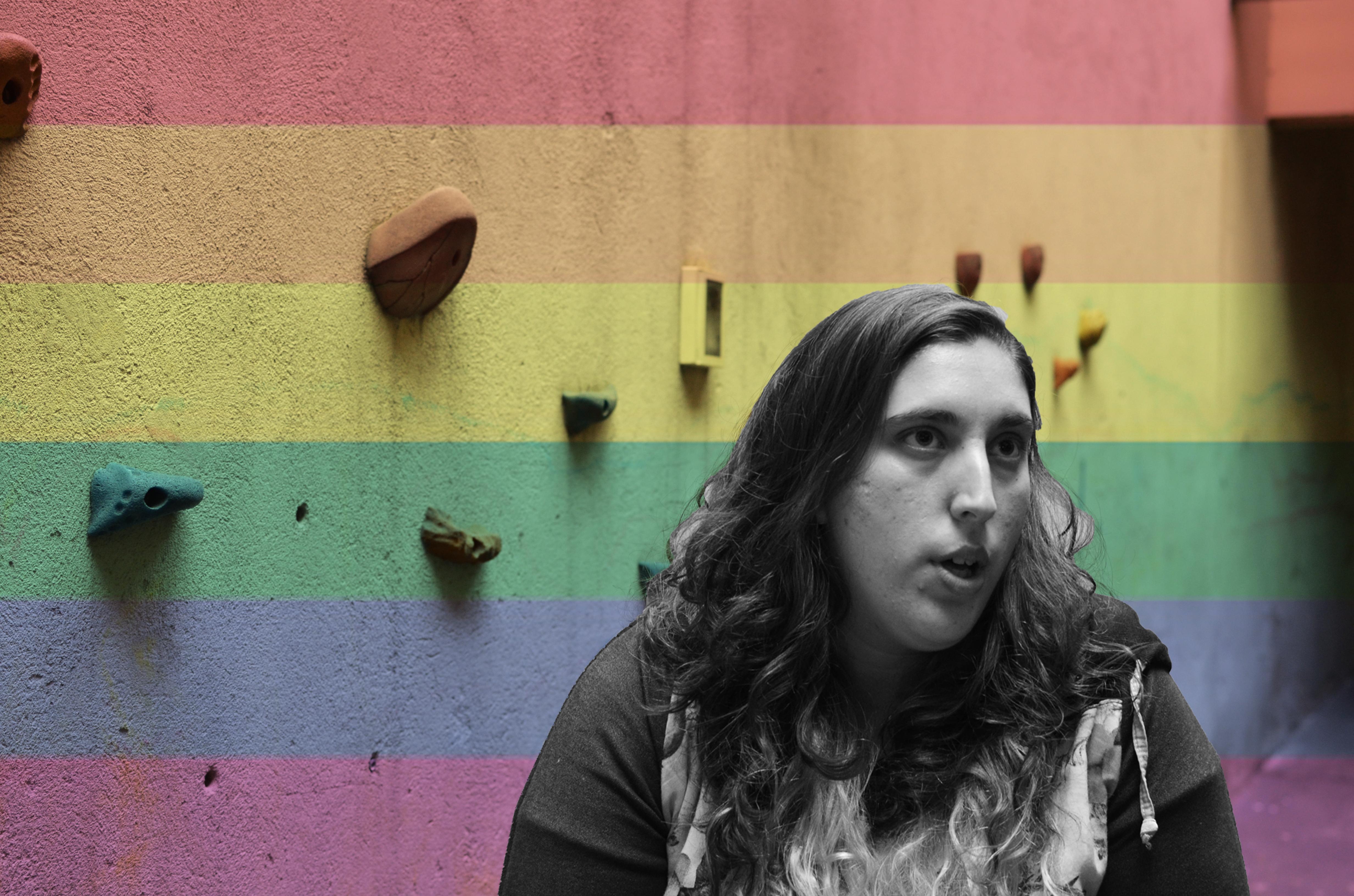 Foto donde aparece Dani en la parte inferior derecha en blanco y negro, con fondo de bandera arcoíris.