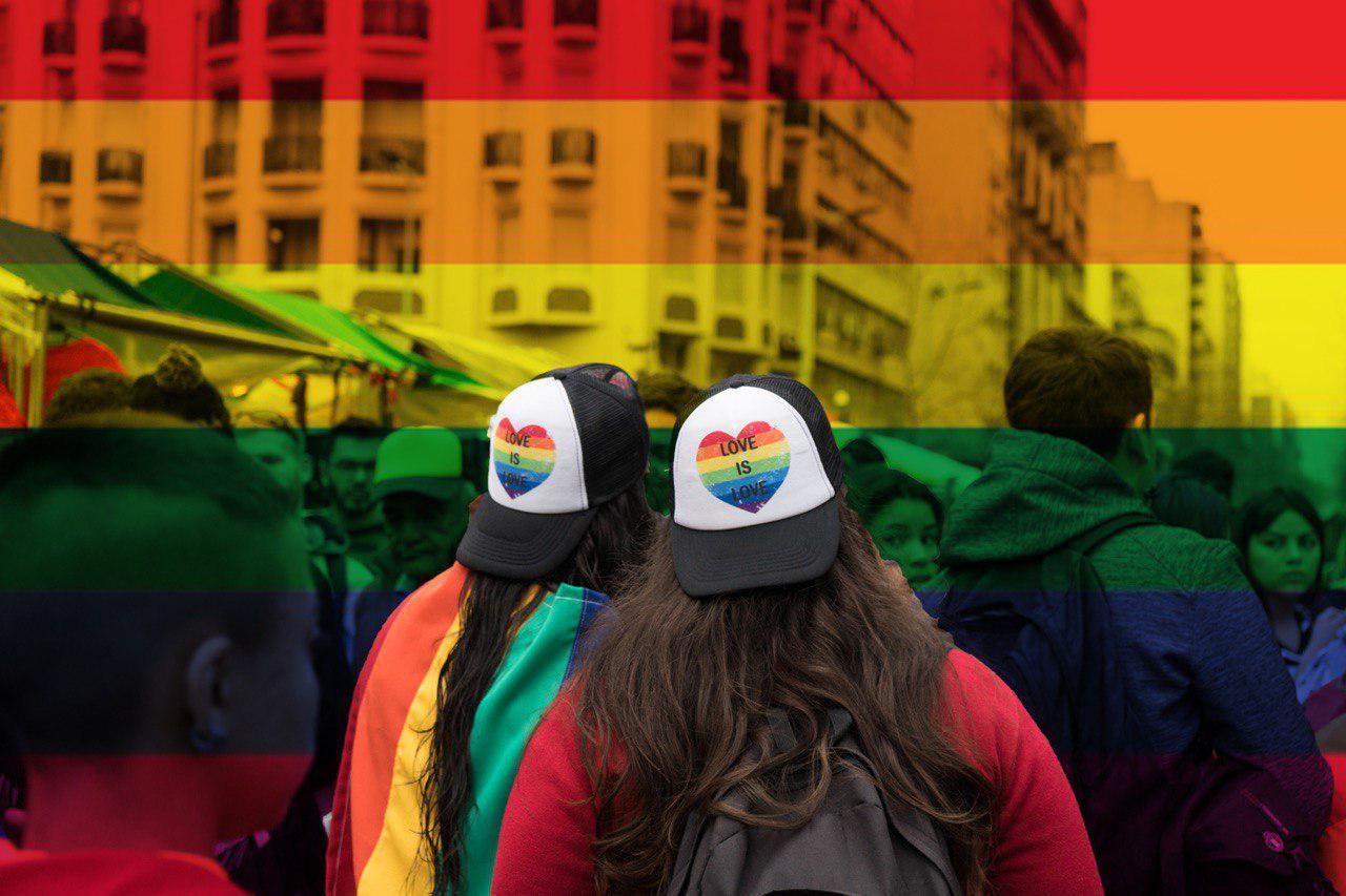 """Dos chicas con gorros con la frase """"love is love"""" y la bandera LGBTI de fondo"""