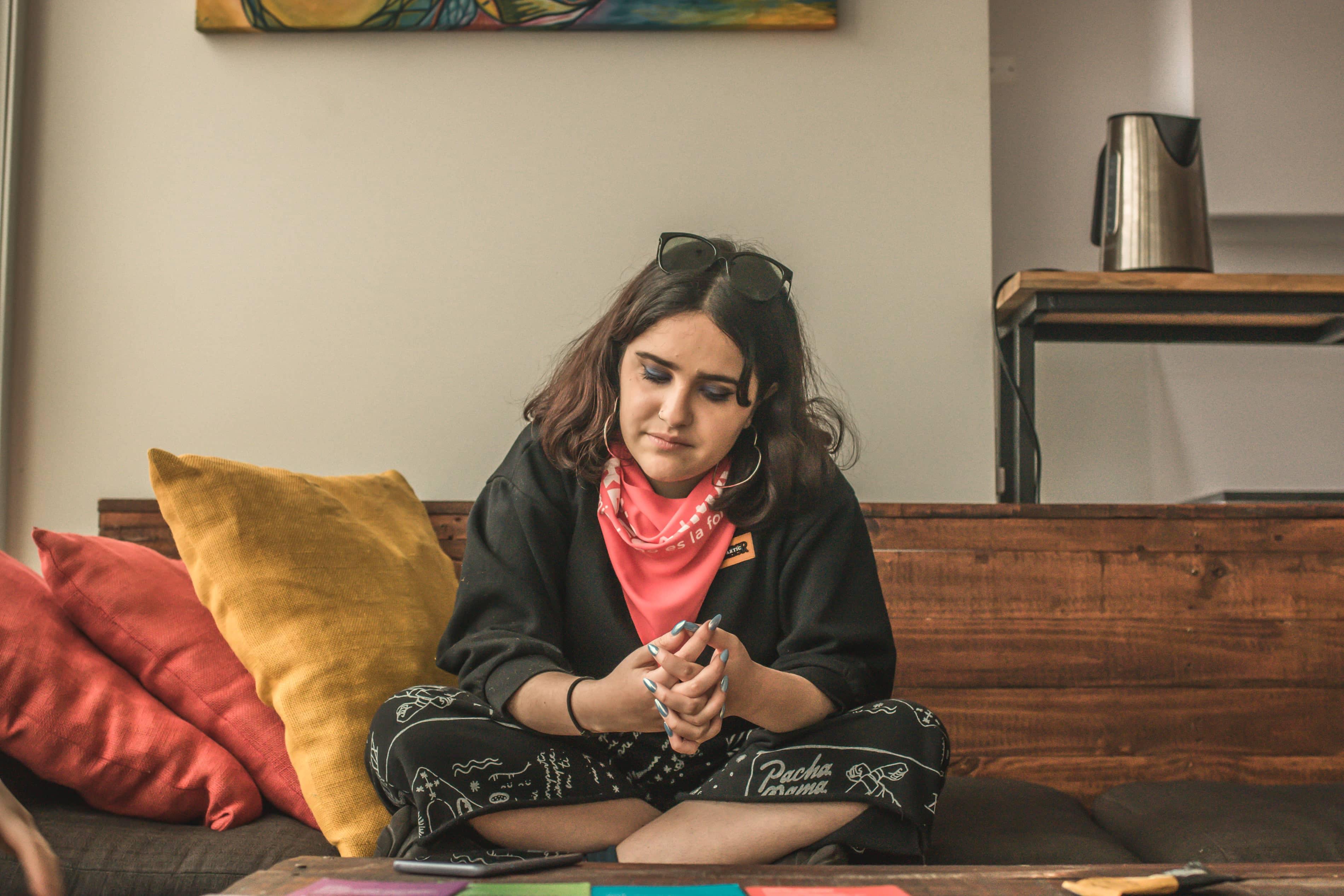 Ofelia sentada en un sillón con los ojos entrecerrados y el pañuelo de No a la Reforma en el cuello.