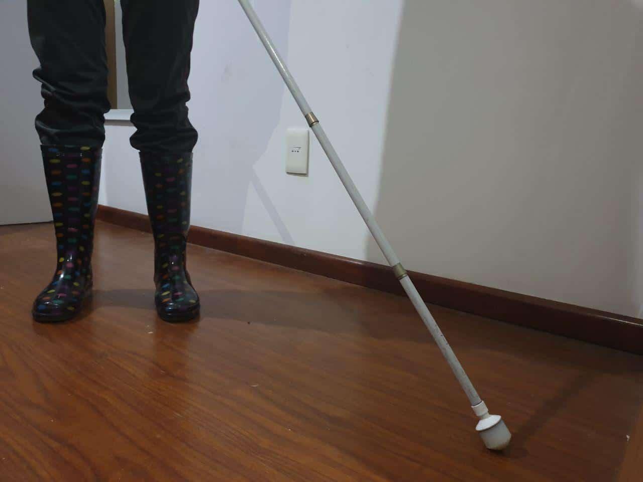 Se muestran unas botas de lluvia con un bastón blanco