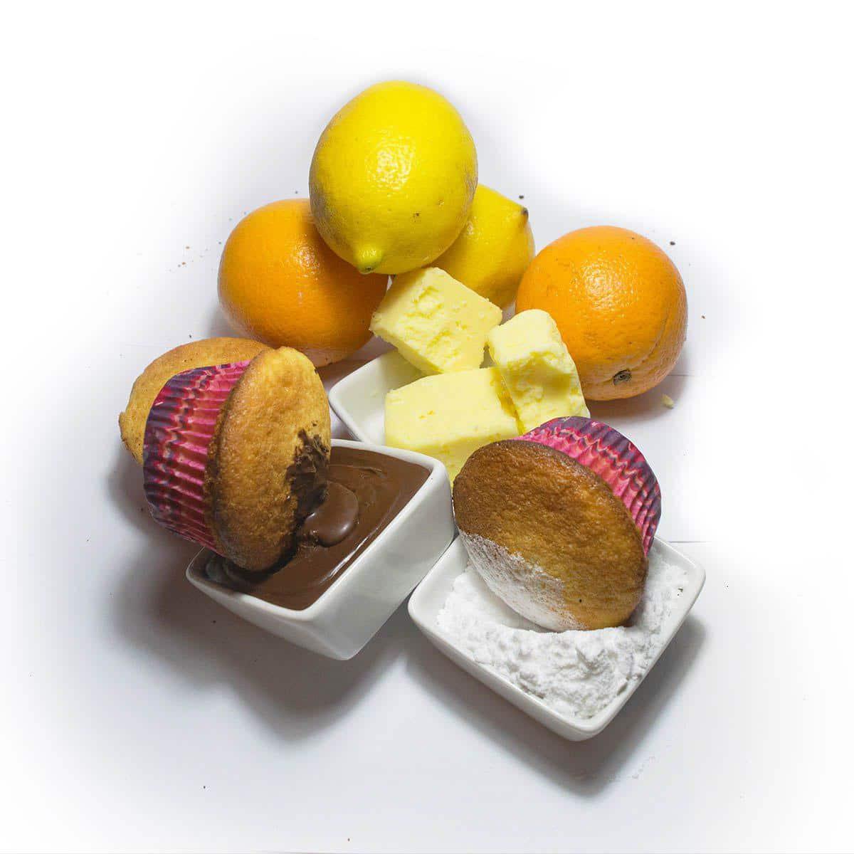 Dos muffins, uno con un baño de chocolate, otro con azúcar impalpable. Atrás de los mismos hay naranjas, limones y manteca