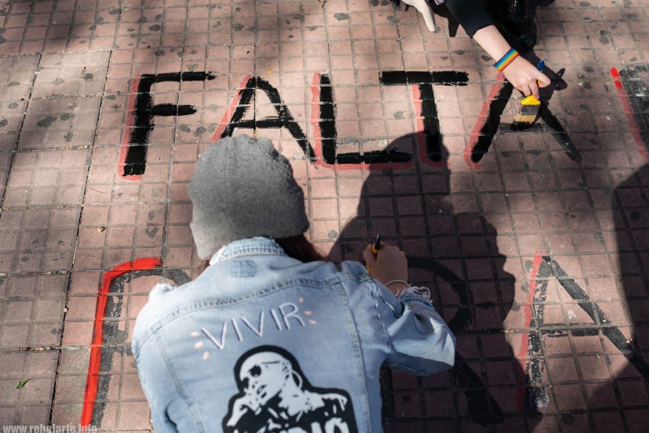 Foto de estudiante del gremio escribiendo con pintura en la calle